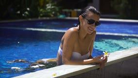 La jeune fille avec les lunettes de soleil noires dans le maillot de bain blanc est sortie la moitié de la piscine et les jeux ro banque de vidéos