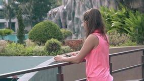 La jeune fille avec la longue queue de cheval se tient prêt la barrière en métal de balcon banque de vidéos