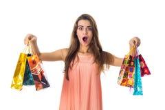 La jeune fille avec surprise énorme tient les sacs lumineux de côtés que des dons est isolés sur le fond blanc Image libre de droits