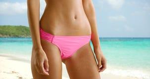 La jeune fille blanche pose à ses fonds de bikini sur les sables blancs du St Photos stock