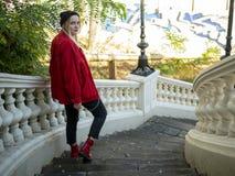 La jeune fille blonde dans un chapeau noir tricoté et des chaussures de veste et rouges rouges relève vers le bas d'une feuille d photo libre de droits