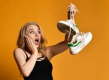 La jeune fille blonde est très étonnée par sa découverte - vieille paire de chaussures sales photo stock