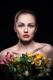 La jeune fille blonde garde des fleurs sur le fond noir Photographie stock libre de droits