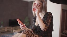 La jeune fille blonde heureuse à l'aide du smartphone communique avec l'ami s'asseyant sur la table banque de vidéos