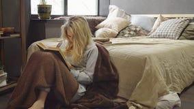 La jeune fille blonde s'assied sur le plancher dans une couverture à côté du lit et lit un livre photos libres de droits
