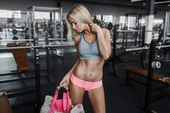 La jeune fille blonde sexy sportive se prépare à l'exercice avec le sac Images stock