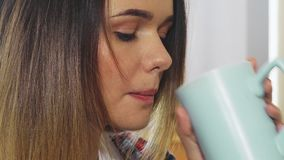 La jeune fille boit d'une tasse banque de vidéos