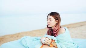 La jeune fille boit du café sur la plage banque de vidéos