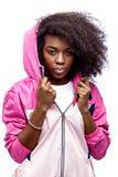 La jeune fille châtain bouclée de mod habillée dans la veste de sports à capuchon rose pose au fond blanc dans le studio images stock