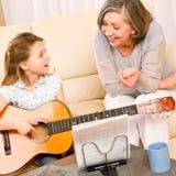 La jeune fille chantent la guitare de pièce au grand-mère Photographie stock