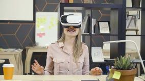 La jeune fille créative emploie des verres de vr sur le lieu de travail banque de vidéos