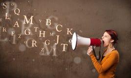 La jeune fille criant dans le mégaphone et le texte sortent Photo libre de droits