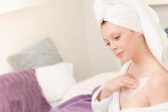 La jeune fille d'étudiant appliquent la lotion de crème corporelle Photos stock