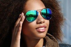 La jeune fille d'afro-américain dans des lunettes de soleil, posant dehors, a habillé occasionnel, avec les cheveux volumineux co photo libre de droits