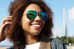 La jeune fille d'afro-américain dans des lunettes de soleil, posant dehors, a habillé occasionnel, avec les cheveux volumineux co image libre de droits