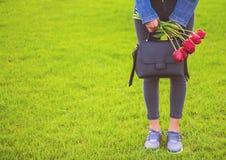 La jeune fille dans des jeans avec le bouquet des fleurs et du sac de tulipes marche en parc Photo stock
