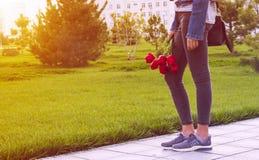 La jeune fille dans des jeans avec le bouquet des fleurs et du sac de tulipes marche en parc Photographie stock