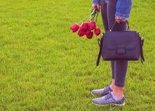La jeune fille dans des jeans avec le bouquet des fleurs et du sac de tulipes marche en parc Images stock