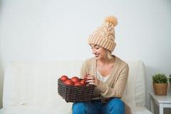 La jeune fille dans des vêtements tricotés confortables tiennent le panier de décoration de boules de Noël Image stock