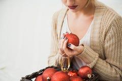 La jeune fille dans des vêtements tricotés confortables tiennent le panier de décoration de boules de Noël Photo stock