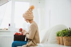 La jeune fille dans des vêtements tricotés confortables tiennent le panier de décoration de boules de Noël Images stock
