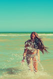 La jeune fille dans l'eau de mer éclabousse et sourire Photographie stock libre de droits