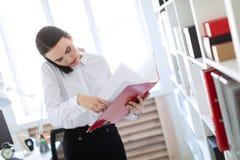 La jeune fille dans le bureau près du support et des parcourir le dossier avec les documents et parle du téléphone image libre de droits