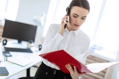 La jeune fille dans le bureau près du support et des parcourir le dossier avec les documents et parle du téléphone images stock