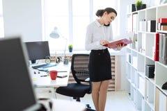 La jeune fille dans le bureau près du support et des parcourir le dossier avec les documents et parle du téléphone photographie stock