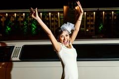 La jeune fille dans la robe et le chapeau blancs pleure hors du bonheur près de la limousine dans la ville de nuit Photos stock