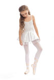 La jeune fille dans sa danse vêtx l'atteinte vers le bas pour toucher son pied Images libres de droits