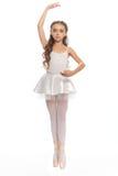 La jeune fille dans sa danse vêtx l'atteinte vers le bas pour toucher son pied Image stock
