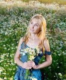 La jeune fille dans un bain de soleil de blues-jean avec un bouquet des fleurs sauvages Images libres de droits