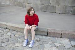 La jeune fille dans un chandail rouge de laine et des shorts de jeans s'assied sur les étapes Image stock