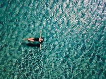 La jeune fille dans un maillot de bain noir nage en mer photo stock