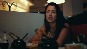 La jeune fille de brune s'asseyent à la table dans le restaurant de sushi Communiquez avec quelqu'un banque de vidéos