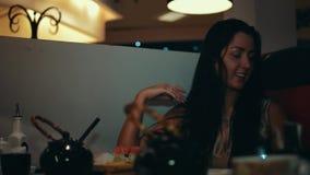 La jeune fille de brune s'asseyent à la table dans le restaurant de sushi Lisez le texte sur le papier entretien clips vidéos