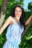 La jeune fille de brunette reste dans une robe bleue Photo stock