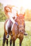 La jeune fille de cavalier s'est pliée au cheval pour complimenter Images stock