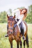 La jeune fille de cavalier s'est pliée au cheval pour complimenter Images libres de droits