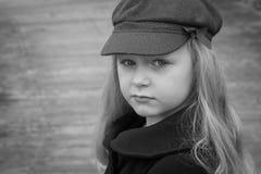La jeune fille de cheveux blonds avec une disposition sérieuse s'est habillée pour l'hiver dans un manteau de laine et un chapeau Photo stock