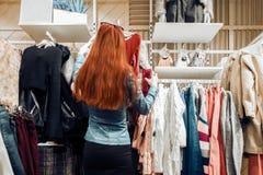 La jeune fille de cheveux rouges dans une veste en cuir bleue choisit des vêtements dans un magasin photo stock