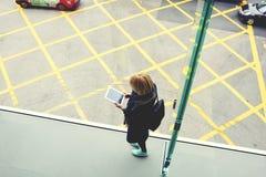 La jeune fille de hippie lit l'information dans le réseau sur le comprimé numérique Photo stock