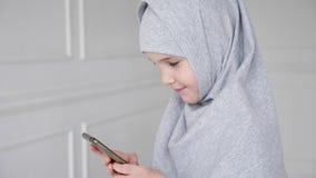 La jeune fille de l'adolescence musulmane dans le hijab joue le smartphone, timidement regardant la cam?ra et le sourire banque de vidéos