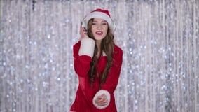 La jeune fille de neige chante des chansons de Noël dans des ses écouteurs Fond de Bokeh clips vidéos