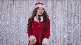 La jeune fille de neige dans le costume chante des chansons dans un rétro microphone Fond de Bokeh clips vidéos