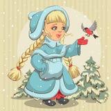 La jeune fille de neige dans le manteau de fourrure bleu alimente le bouvreuil Image stock