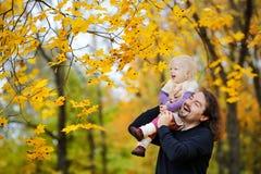 La jeune fille de père et d'enfant en bas âge ont l'amusement à l'automne Photo libre de droits