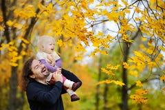 La jeune fille de père et d'enfant en bas âge ont l'amusement à l'automne Photographie stock