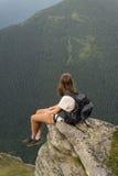 La jeune fille de randonneur se repose sur la falaise et apprécie le paysage stupéfiant des montagnes couvertes de forêts de pin Photo stock